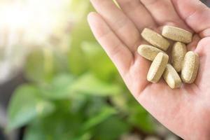 Draufsicht der Tablette der alternativen organischen Medizin auf der Hand der Frau foto