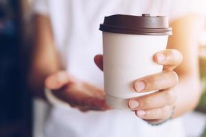 Hand hält eine Tasse Kaffee mit Sonnenlicht Fackel foto
