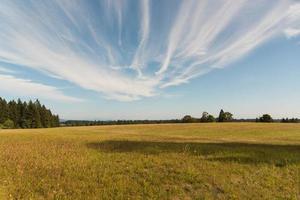großes leeres Feld unter Wolken foto