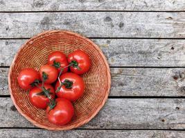 Tomaten in einem Weidenkorb auf einem hölzernen Tischhintergrund foto