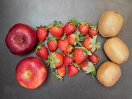 Erdbeeren, Kiwis und Äpfel auf einem dunklen Holztischhintergrund foto