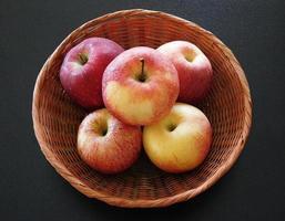 fünf Äpfel in einem Weidenkorb auf einem dunklen Tischhintergrund foto