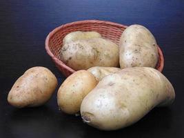 Kartoffeln in einem Weidenkorb auf einem dunklen Hintergrund foto