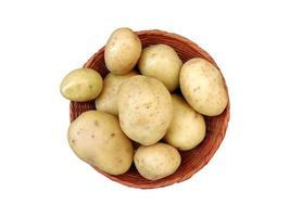Kartoffeln in einem Weidenkorb auf einem weißen Hintergrund foto