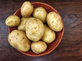 Kartoffeln in einem Weidenkorb auf einem dunklen Holztischhintergrund foto