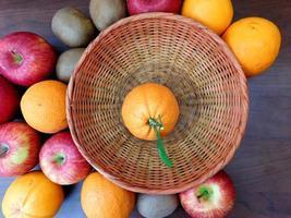 Orange in einem Weidenkorb neben Orangen, Äpfeln und Kiwis auf einem dunklen Holztischhintergrund foto