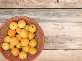Aprikosen in einem Weidenkorb auf Holztischhintergrund
