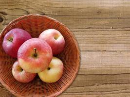 fünf Äpfel in einem Weidenkorb auf einem Holztischhintergrund foto