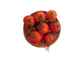 Tomaten in einem Weidenkorb auf einem weißen Hintergrund foto