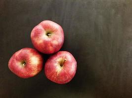 drei Äpfel auf einem dunklen Tischhintergrund foto