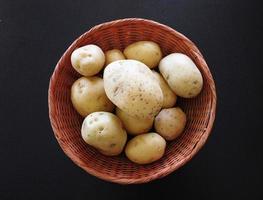 Kartoffeln in einem Weidenkorb auf einem dunklen Tischhintergrund
