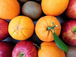 Orangen, Kiwis und Äpfel auf einem dunklen Holztischhintergrund foto