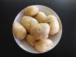 Kartoffeln in einer weißen Schüssel auf einem dunklen Tischhintergrund