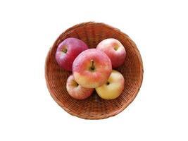 fünf Äpfel in einem Weidenkorb auf weißem Grund foto