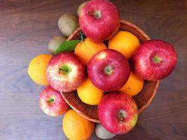 Orangen und Äpfel in einem Weidenkorb auf einem dunklen Holztischhintergrund foto
