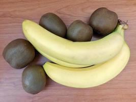 Kiwis und Bananen auf einem dunklen Holztischhintergrund foto