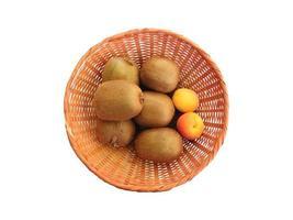 Kiwis und gelbe Äpfel in einem Weidenkorb auf weißem Grund foto