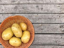 Kartoffeln in einem Weidenkorb auf einem Holztischhintergrund