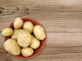Kartoffeln in einem Weidenkorb auf einem Holztischhintergrund foto