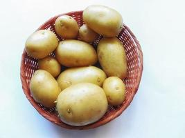 Kartoffeln in einem Weidenkorb auf einem blauen Hintergrund