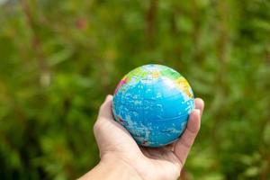 menschliche Hand hält einen grünen Planeten, rette das Erdkonzept