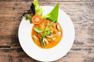 Draufsicht des roten Curry mit Huhn auf einem hölzernen Hintergrund