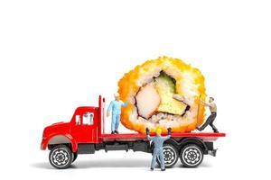 Miniaturmenschen mit Sushi-Rollen auf einem LKW lokalisiert auf einem weißen Hintergrund, Lebensmittellieferungskonzept foto