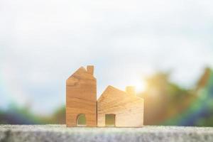 Holzhausmodell mit einem Himmelhintergrund-, Wohnungs- und Immobilienkonzept