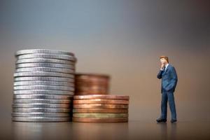 Miniatur-Kleinunternehmer, die mit einem Stapel von Münzen stehen, Geschäftswachstumskonzept