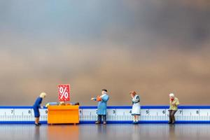 Miniaturmenschen, die Distanz einkaufen, soziales Distanzierungskonzept foto