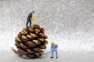 Miniaturarbeiter, die einen Weihnachts-Tannenzapfen, Weihnachten und ein frohes neues Jahr-Konzept vorbereiten foto