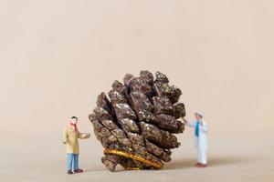 Miniaturarbeiter, die eine Weihnachtsdekoration, Weihnachten und ein frohes neues Jahr-Konzept malen foto