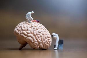 Miniaturleute von Wissenschaftlern, die das Konzept des menschlichen Gehirns, der medizinischen Gesundheitsversorgung und des chirurgischen Arztes beobachten foto