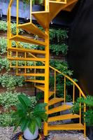 gelbe Wendeltreppe mit Pflanzen auf Backsteinmauer foto