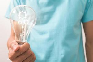 ein Mann, der eine Glühbirne mit einem Zahnradsymbol hält foto