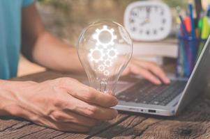 ein Mann, der ein Glühbirnen-Zahnradsymbol hält, während er einen Computer benutzt foto