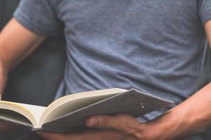 ein Mann, der in ein Notizbuch schreibt foto