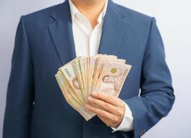 Geschäftsmann, der thailändisches Geld hält