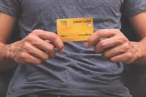 ein Mann, der eine Kreditkarte in der Hand hält