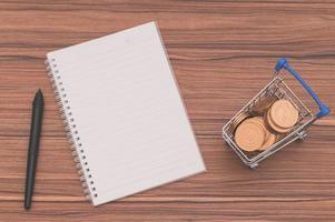 Notizbuch auf dem Schreibtisch mit Münzen in einem winzigen Wagen