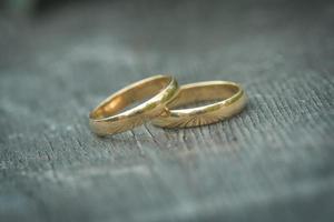 ein Paar goldene Eheringe mit Bokeh-Hintergrund foto