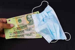 Gesichtsmaske mit vietnamesischem Geld auf schwarzem Hintergrund foto