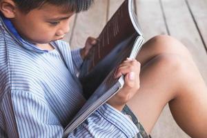 Junge sitzt und liest ein Buch auf Holzboden foto