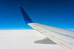 Flugzeugflügel über weißen Wolken