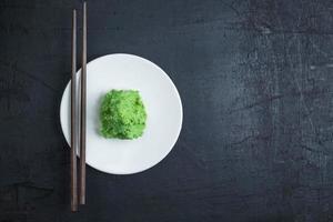 Wasabi auf weißem Teller mit Essstäbchenpaar auf schwarzem Tischhintergrund foto
