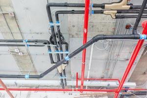Lüftungsrohre aus Isoliermaterial und Sprinkler auf rotem Rohr foto