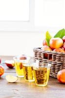 Apfelsaft in Gläsern und Äpfeln im Korb
