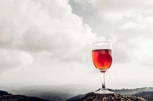 ein Glas Roséwein vor einer bergigen Landschaft