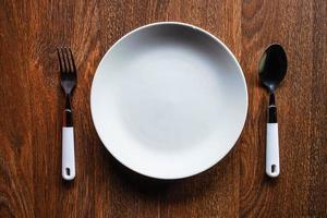 weißer Teller mit einem Löffel und einer Gabel auf einem Holztisch