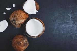 Kokosnuss halbiert auf einem schwarzen Tischhintergrund